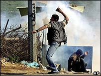 A Palestinian throws a stone near the Erez crossing point