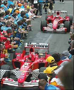 Schumacher is feted by the Ferrari team as he leads Barrichello into parc ferme