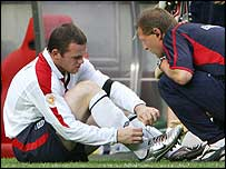 Wayne Rooney is treated for his injury against Portugal