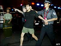 Chinese police detain a football fan during unrest following the Asian Cup final