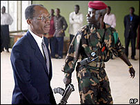 Jean-Bertrand Aristide accompanied by a soldier to a news conference in Central African Republic