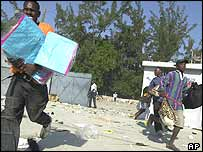Looters make off with items from a complex near the airport in Port-au-Prince