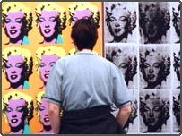 A visitor studies Andy Warhol's Marilyn Diptych painting at the Tate Modern in central London