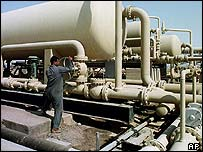 An Iraqi oil field worker checks pipes at the West Qurna oil field in Iraq