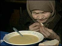 Old Russian woman eating bread