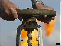 Worker turns on valve at oilfield