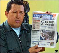 Hugo Ch�vez muestra un peri�dico de la oposici�n.