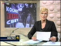 Serbian TV newsreader, with backdrop reading: Kosovo, terror, world