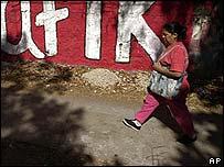 Mujer caminando frente a un muro pintado con propaganda pol�tica.