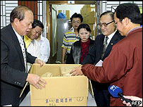 Taiwanese election committee officials seal ballot boxes