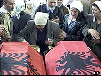 Woman weeps over coffins of two young Albanian boys at funeral in Cabra, Kosovo