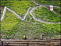 Venezuelan farmers walk in a field in which the word No has been carved