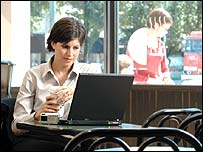 Woman using wi-fi internet access in a cafe