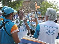 Eric Falt, left, receives the Olympic Torch from Jean-Michel Cousteau
