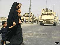 An Iraqi woman and her children walk past US military armoured vehicles in Najaf on Friday