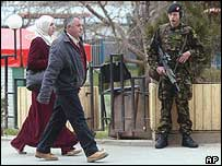 Kosovo Albanians pass by a British soldier patrolling a main road in capital Pristina