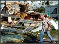 A man walks by a destroyed mobile home in Harborview Park in Port Charlotte, Florida