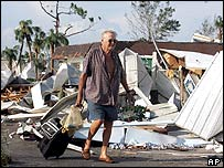 A man pulls belongings out of the wreckage of a mobile home park in Punta Gorda
