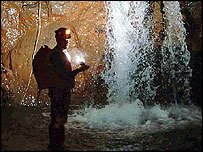 Expedition member by waterfall, courtesy of Combined Services Caving Association