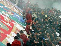 Pilgrims get close to touch a huge silk portrait of the Sakyamuni Buddha on a hillside above the Drepung Monastery in Lhasa, the capital of Tibet
