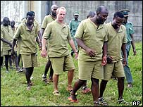 A group of alleged mercenaries are led to a hall at Chikurubi maximum prison