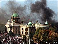 Smoke rises behind federal parliament in Belgrade during anti-Milosevic protest