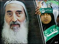 A woman in Gaza City holds a poster of Hamas spiritual leader Sheik Yassin