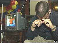 An opposition supporter sobs as Mr Chavez delivers his victory speech on TV