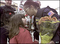 An American police officer receiving flowers from a Kosovo Albanian girl