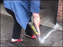 woman paints tram line along her driveway