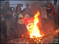Opposition supporters burn flags from the pro-Chavez campaign