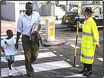 Lollipop lady on a zebra crossing with child and parent