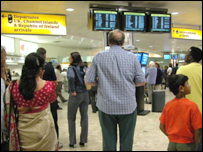 Passengers looking at flight information screens