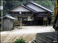 Flood waters pass in front of a house in southern Japan