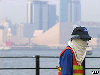 A worker with face wrapped with a towel walks along the Tsim Sha Tsui promenade in Hong Kong (18 August 2004)