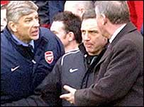 Fourth official Alan Wiley is between a rock and a hard place as Arsene Wenger (left) and Sir Alex Ferguson clash on the touchline