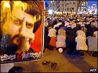Protesters pray at the offices of Al-Hawza