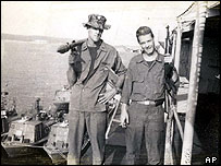 John Kerry (L) and William Rood pose in Vietnam with captured weapons