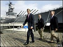 John Kerry passes a mothballed battleship in Norfolk, Virginia