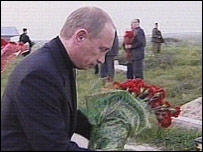 Russian President Vladimir Putin lays flowers by the graveside