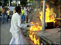 Protesters set fire to a tea stall in Dhaka