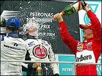 Juan Pablo Montoya (left) and Michael Schumacher spray Jenson Button with champagne in Malaysia