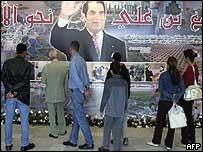 People stand in front of a giant poster showing President Ben Ali, celebrating his 16 years in power, last November
