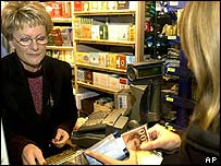A woman hands over money in a French shop