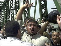 Iraqis celebrate after hanging the corpses on a bridge
