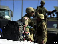 An unexploded bomb is guarded by US troops near Baghdad