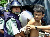 Riot police detain an opposition activist during the general strike in Dhaka