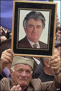 An elderly supporter in the national Serbian cap holds up a photo of Radovan Karadzic