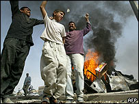 Iraqis dance near a burning car in the flashpoint town of Falluja, 31 March 2004
