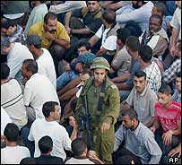 Detained Palestinians surrounding an Israeli soldier